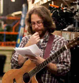 Ask Me Another house musician, Jonathan Coulton, puzzles over papers before a show taping.