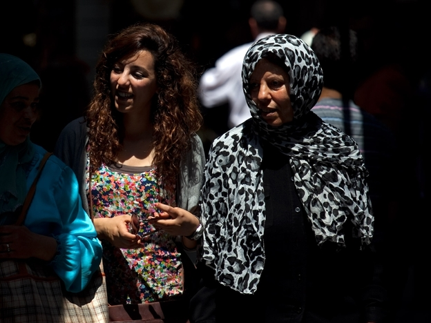 Tunisian women walk through the narrow streets of Tunis' medina, or marketplace. Compared to women in other Arab countries, Tunisian women have had access to education and job opportunities for decades.