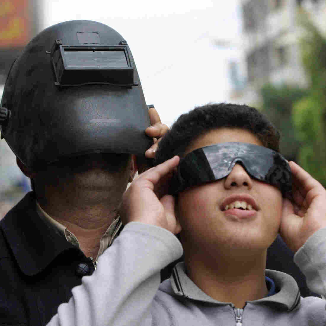 Safety over style: In 2006, a Palestinian man and boy were careful to protect their eyes while watching a partial eclipse of the sun. The same cautions are in order for Venus' transit of the sun on Tuesday.