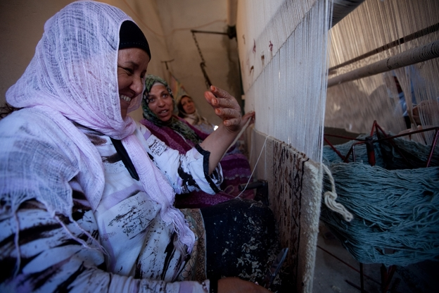 Workers at a carpet-making business in the town of Kairouan are paid about $2.50 a day. Many carpet buyers are tourists, but the number of foreign visitors has dropped since the revolution. (NPR)