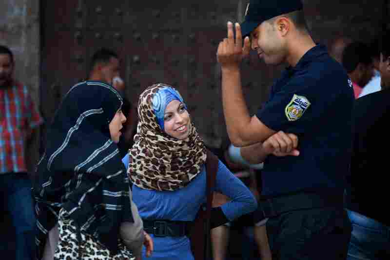 Women talk with a police officer in Tunis.
