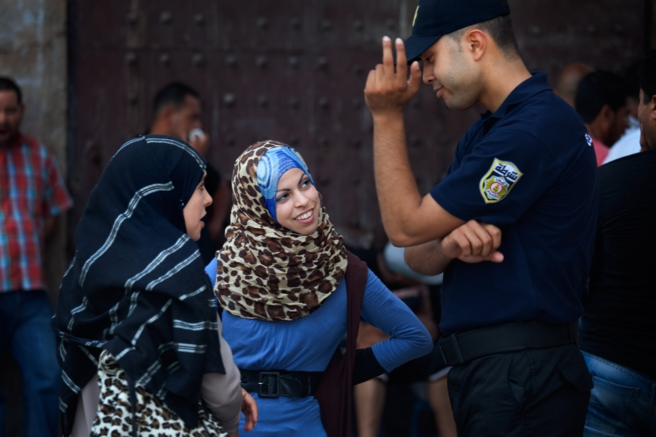 Women talk with a police officer in Tunis. (NPR)
