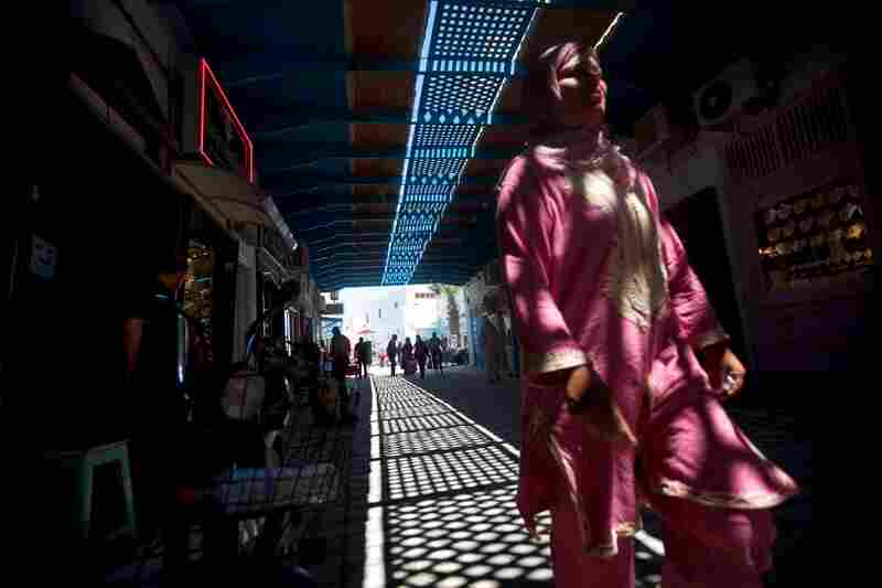 A woman walks through the marketplace in Kairouan, where some street scenes from Raiders of the Lost Ark were filmed.