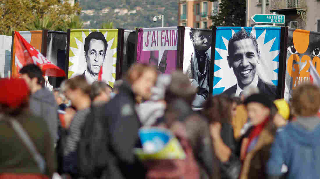 Protesters in Nice, France, hold banners depicting then-French President Nicolas Sarkozy and President Obama before a November 2011 G-20 summit where global financial issues were discussed. Sarkozy has since lost re-election; some political scientists say economic problems in Europe also could play an unprecedented role in the upcoming U.S. election.
