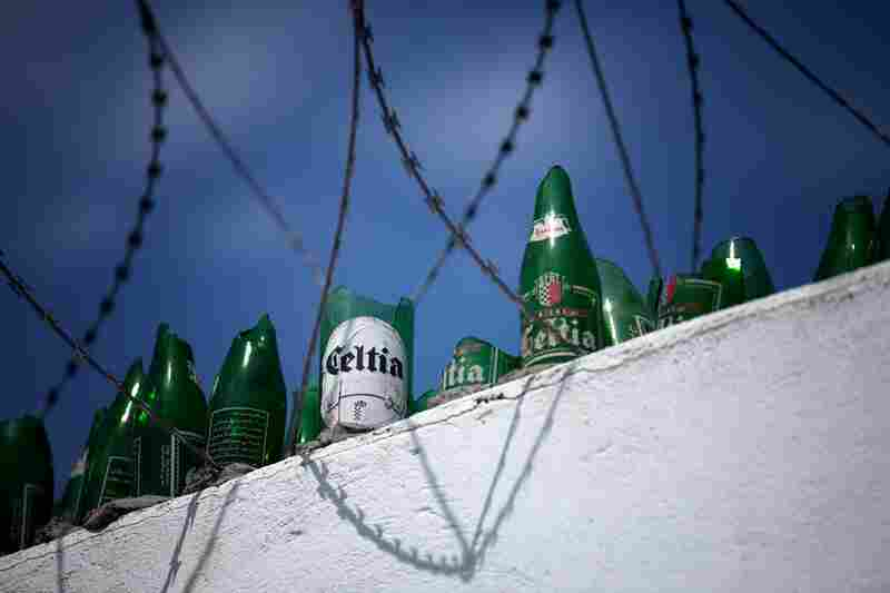 The wall surrounding the Celtia brewery is about 12-feet high and topped with razor wire and broken beer bottles. The brewery is owned by the state, and the governm