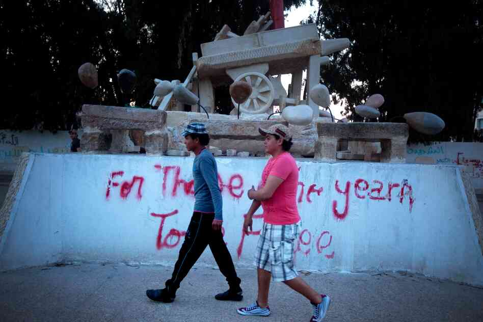 "A monument to Mohammed Bouazizi, a fruit seller who touched off the Arab Spring by setting himself on fire in the central Tunisian town of Sidi Bouzid. The graffiti reads, ""For Those Who Yearn To Be free."""