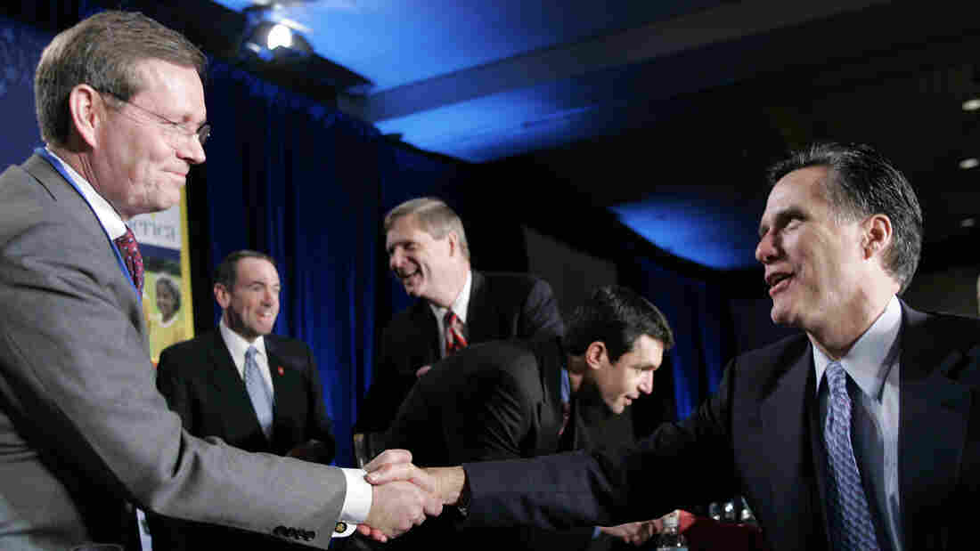 Mitt Romney (right), at the time the governor of Massachusetts, greets then-Health and Human Services Secretary Mike Leavitt during a National Governors Association forum in February 2006. Romney reportedly has tapped Leavitt to head his presidential transition team.