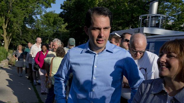 Wisconsin Gov. Scott Walker waits in line to vote Tuesday in Wauwatosa, Wis.