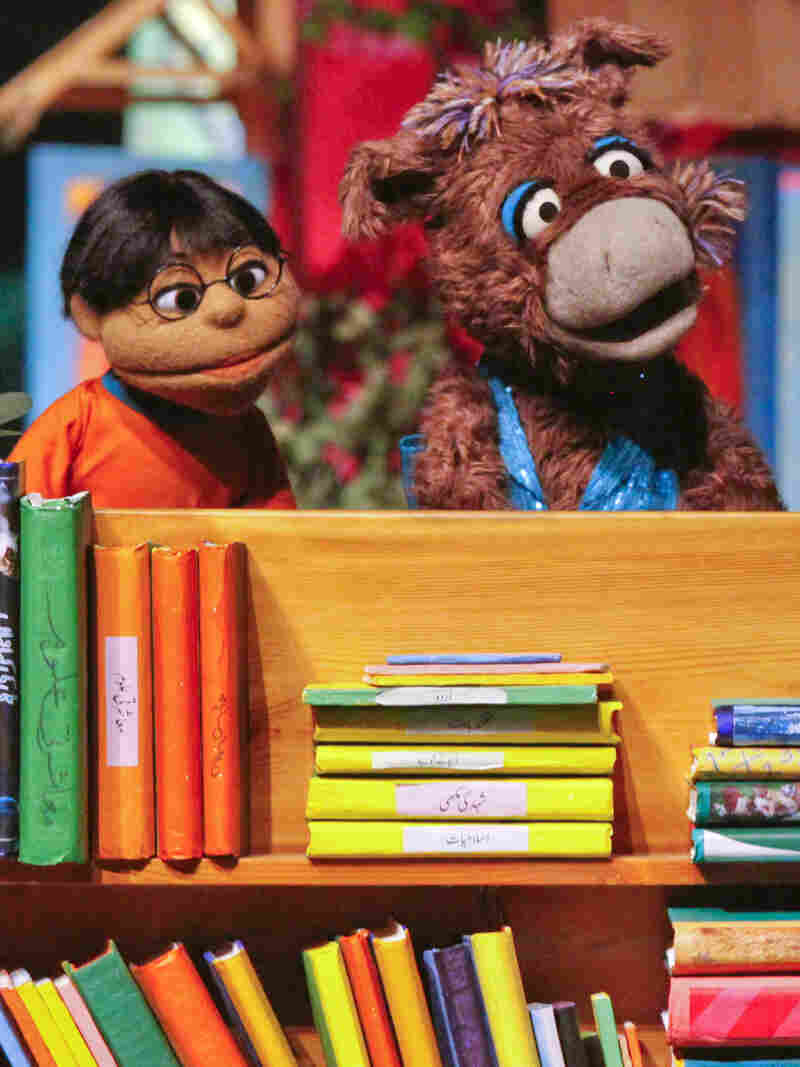 Baily the donkey (right) and Munna, characters from the Pakistani version of Sesame Street, perform at the launch ceremony for the show, Sim Sim Hamara, at Rafi Peer Theater Workshop in Lahore, Nov. 26, 2011.