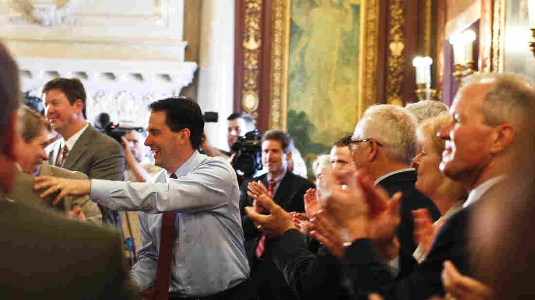 Wisconsin Gov. Scott Walker (center) is greeted by his Cabinet and staff Wednesday at the state Capitol in Madison, a day after defeating Milwaukee Mayor Tom Barrett in a recall election.