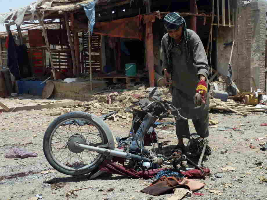 An Afghan man inspects a motorcycle used in today's suicide attack near Kandahar.