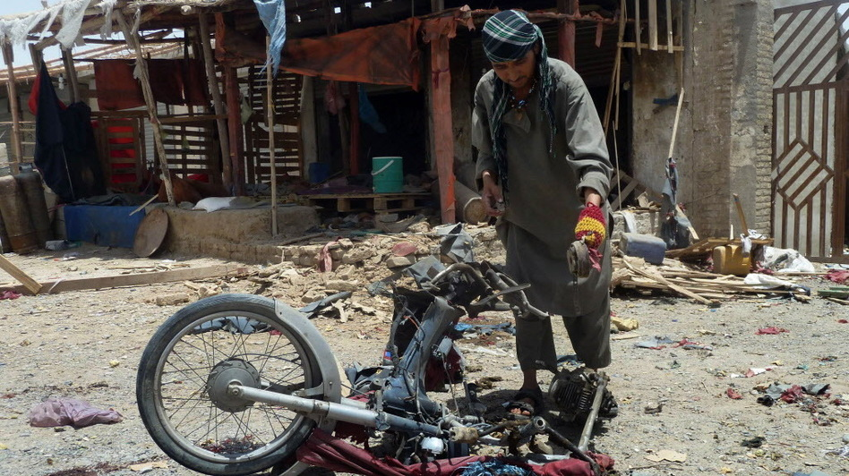 An Afghan man inspects a motorcycle used in today's suicide attack near Kandahar. (AFP/Getty Images)