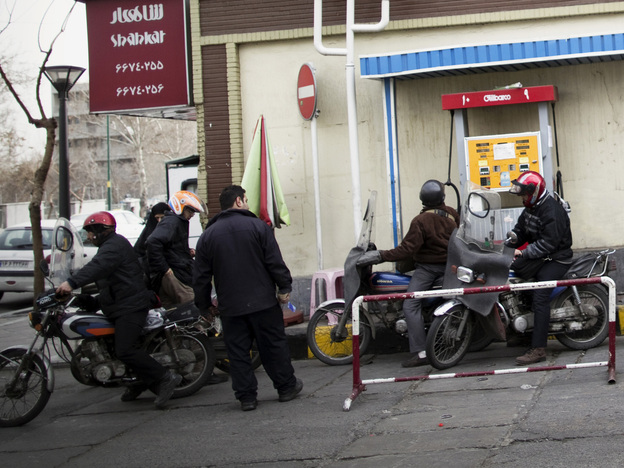 Iranians line up at a gas station to fuel their motorcycles in central Tehran in February. Oil is the lifeblood of Iran's economy, but the planned EU boycott is expected to deal a major blow to Iranian oil exports.