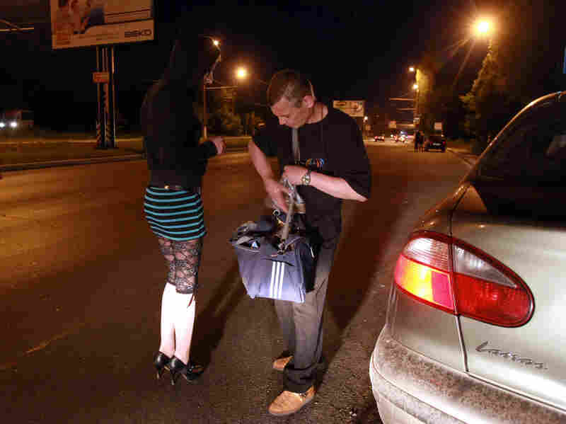 A social worker gives condoms to a sex worker in Kiev.