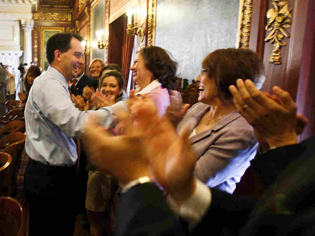 Wisconsin Gov. Scott Walker is greeted by his Cabinet and staff at the state Capitol in Madison on Wednesday, a day after he defeated Milwaukee's Democratic mayor, Tom Barrett, in a recall election.