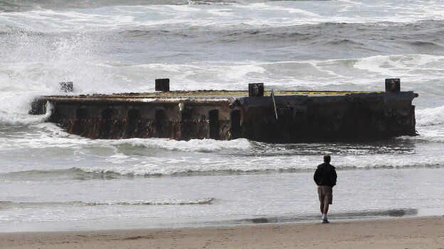 A man looks at the massive dock from Japan that washed ashore on Oregon's Agate Beach this week.