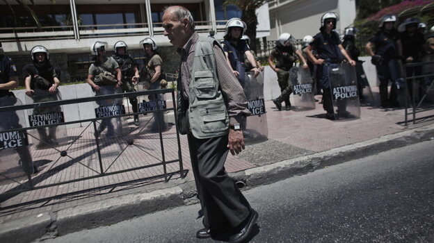 An elderly man walked by riot policemen guarding the Interior Ministry in Athens on Wednesday.