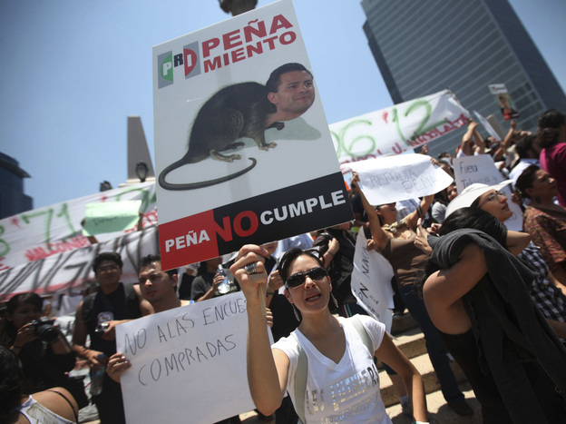 A demonstrator holds an anti-Pena Nieto sign during a May 19 protest against the PRI candidate in Mexico City.