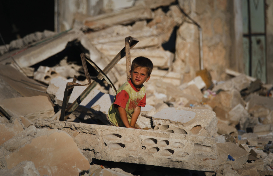 A Syrian boy sits in the rubble of house which was destroyed during a military operation by the Syrian pro-Assad army in April in the town of Taftanaz, Syria.