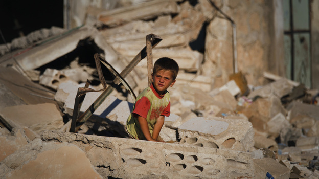 A Syrian boy sits in the rubble of house which was destroyed during a military operation by the Syrian pro-Assad army in April in the town of Taftanaz, Syria. (AP)