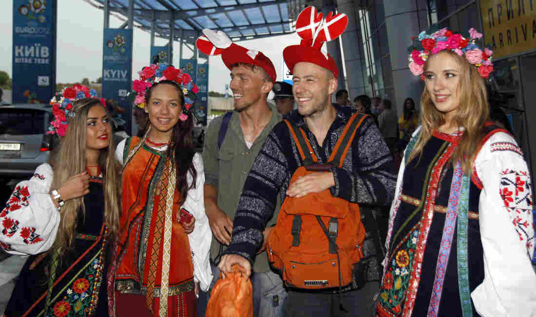 Soccer fans pose with Ukrainian girls dressed in traditional costumes at the airport in Kiev, the capital, Wednesday. The former Soviet state, together with Poland, is co-hosting the Euro 2012 soccer championship.