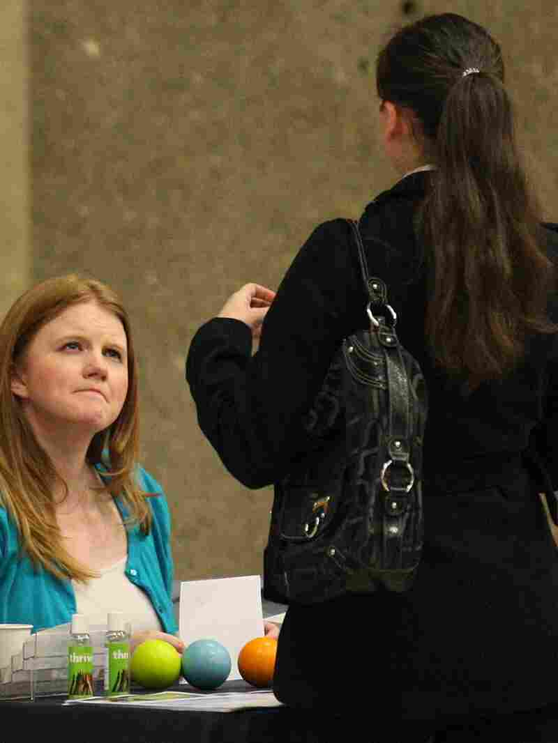 A recruiter (left) talks with a job seeker at an Oregon job fair. Job growth slowed in May, and some employers say economic uncertainty has left them reluctant to hire.