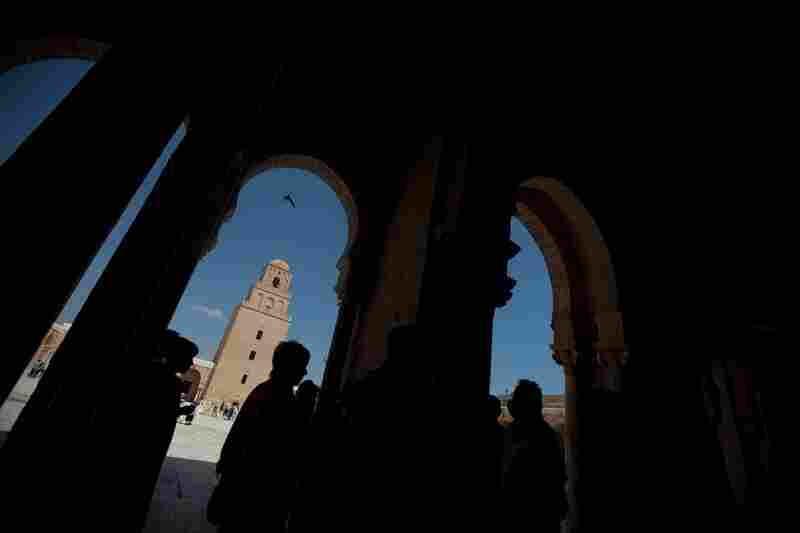 Kairouan is home to scores of places of worship, including the Great Mosque, a building of sandy bricks with a square minaret and a design that is said to have influenced mosques all through the region. Visitors and tourists are silhouetted inside the ancient building.