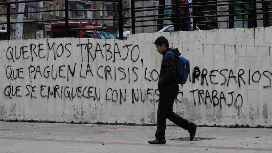 "Graffiti on a wall in Madrid reads, ""We want to work, let the businessmen who have gotten rich from our labor pay for the crisis."" Nearly 50 percent of young adults in Spain are unemployed."