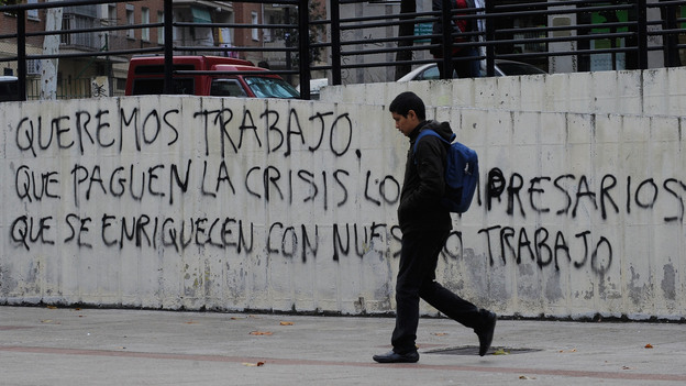 """Graffiti on a wall in Madrid reads, """"We want to work, let the businessmen who have gotten rich from our labor pay for the crisis."""" Nearly 50 percent of young adults in Spain are unemployed. (Getty Images)"""