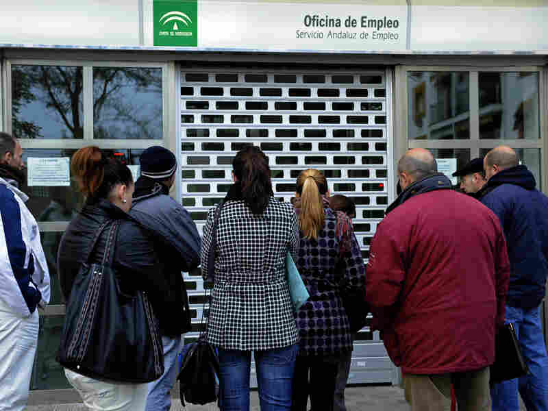 People wait in line in front of a government employment office in the Cruz Roja suburb of Sevilla.
