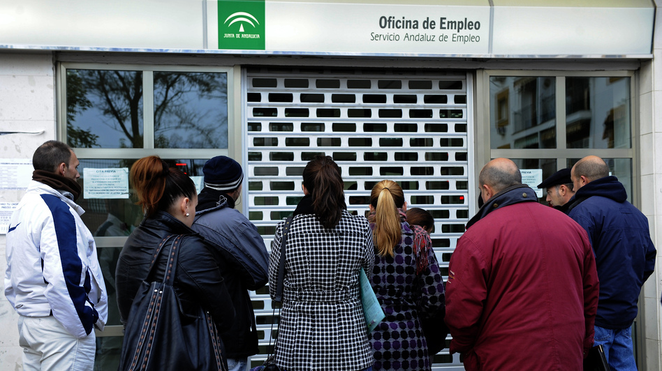 People wait in line in front of a government employment office in the Cruz Roja suburb of Sevilla. (AFP/Getty Images)
