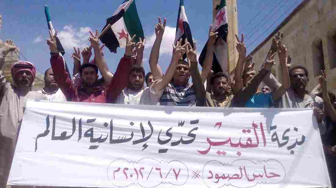 """Anti-government protesters in the northern Syrian village of Hass protest on Thursday following the deaths of dozens of civilians a day earlier in the village of Mazraat al-Qubair. The banner reads, """"The al-Qubair massacre challenges the world's humanity."""""""