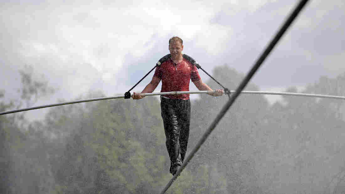 Nik Wallenda walks a tightrope in the rain during a training session for his upcoming stunt in Niagara Falls, N.Y.
