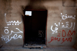 "A destroyed home in Tawargha, south of Misrata. Residents were driven out and have not returned, fearing they will be killed. Graffiti in the town talks of ""slaves,"" a reference to the black-skinned people of Tawargha. The town has been unofficially renamed New Misrata."