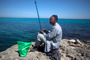 A man fishes in the Mediterranean outside a Tawargha refugee camp on the outskirts Tripoli. The people of Tawargha fled their ancestral homeland after the revolution when people from the city of Misrata accused them of collaborating with Gadhafi.