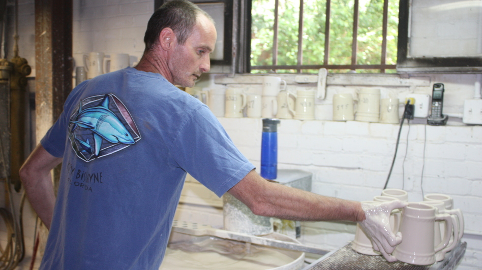 Bob Davis hand-dips mugs before they go into the kiln at American Mug and Stein in East Liverpool, Ohio. Most overseas companies have machines that can do this much faster.