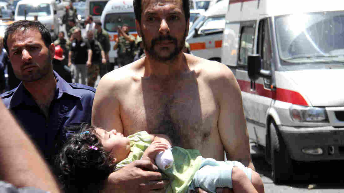 A Syrian man carries a wounded girl next to Red Crescent ambulances following an explosion Friday reportedly targeting a military bus near Qudssaya, a neighborhood in Damascus.