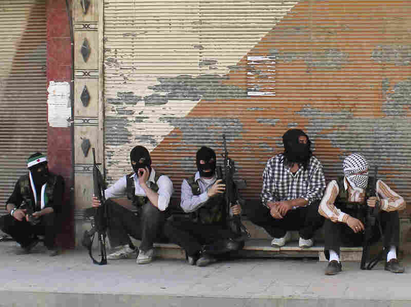 Free Syrian Army members, with covered faces and holding weapons, sit by the side of a street Monday in the Qaboon district in Damascus.