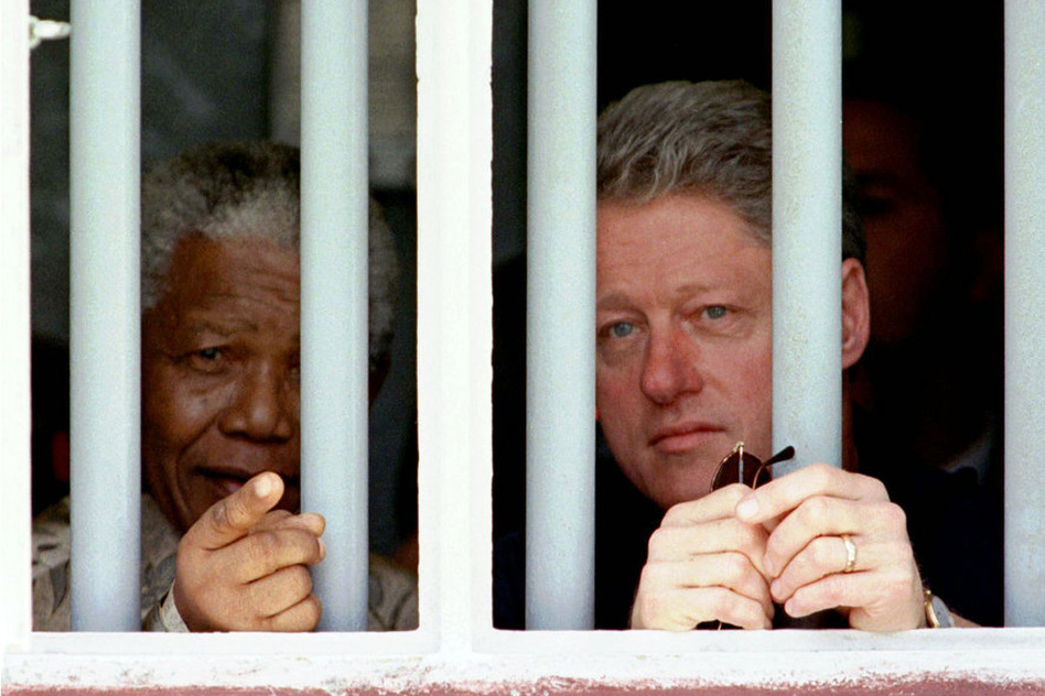 President Bill Clinton and Mandela peer through the bars of Mandela's prison cell on Robben Island, on March 27, 1998. Mandela spent 18 years in the cramped gray cell. (AP)