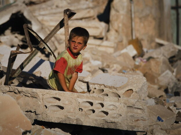 A Syrian boy sits in the rubble of house destroyed during a military operation in April in the town of Taftanaz, Syria.