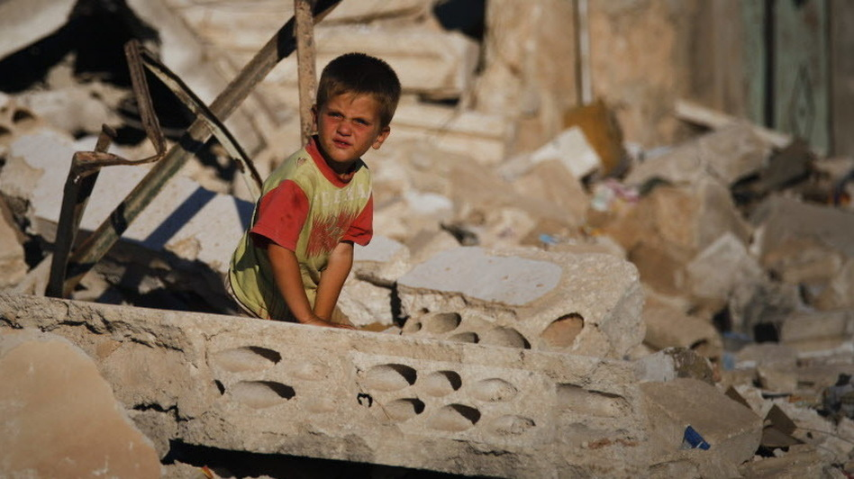 A Syrian boy sits in the rubble of house destroyed during a military operation in April in the town of Taftanaz, Syria. (AP)