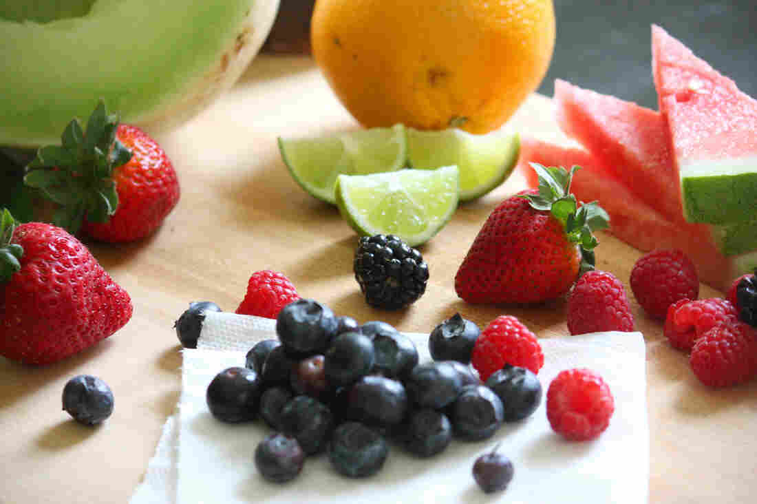 Fruit salad ingredients, including honeydew, watermelon, orange, lime, strawberries, blueberries and raspberries.