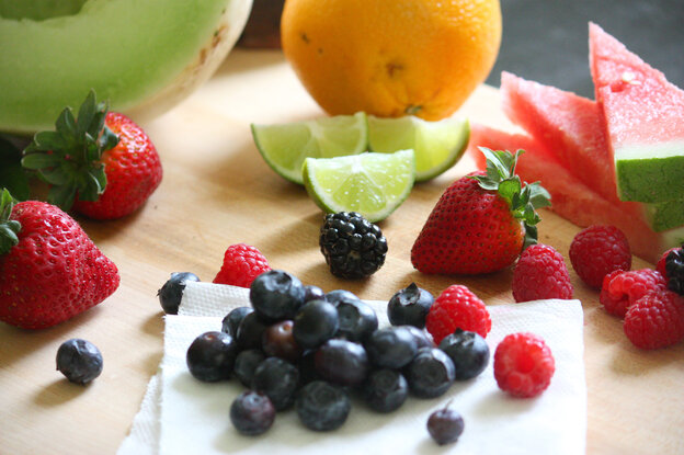 Fruit salad ingredients, including honeydew, watermelon, orange, lime, strawberries, blueberries and raspberries.