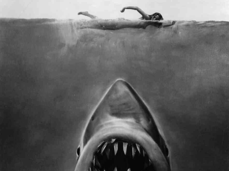 Susan Backlinie swims as the great white shark rises toward her in publicity art for the 1975 film Jaws.