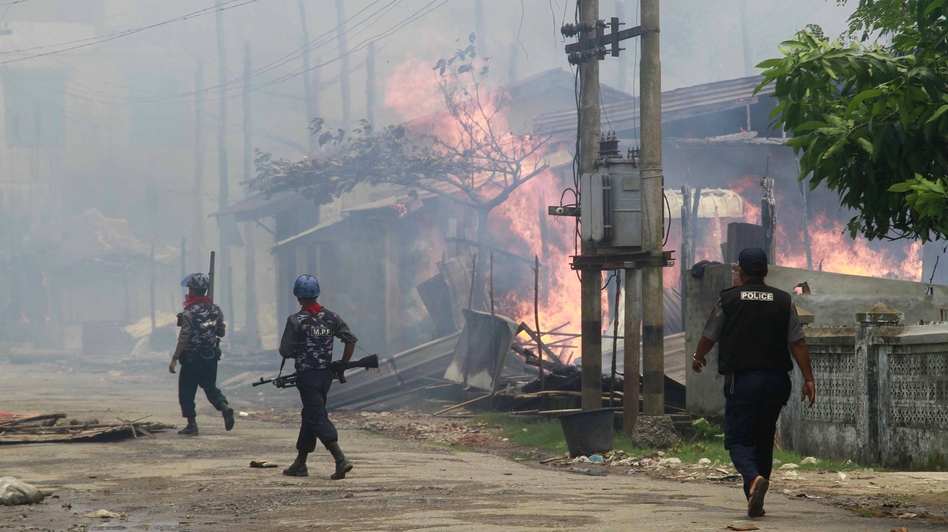 Policemen in Myanmar walk toward burning buildings in the town of Sittwe, in the western part of the country, where Muslims and Buddhists have clashed recently.