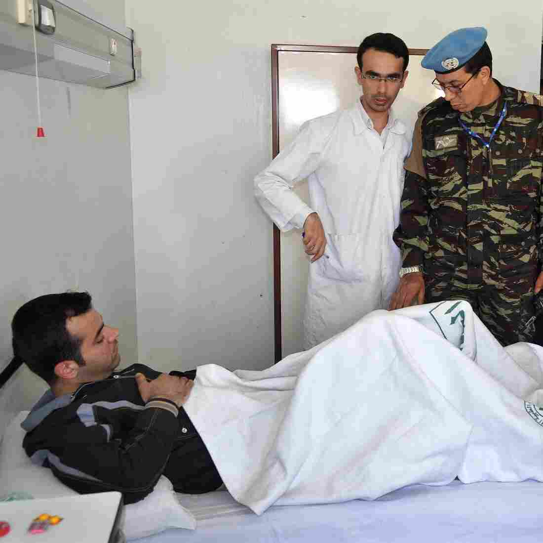 Members of the U.N. observers mission in Syria visit wounded soldiers and policemen at Tishreen Military Hospital in Damascus on May 23. Casualties among Syrian government forces are rising sharply.