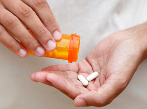 A woman pours two tablets into her hand from a pill bottle.