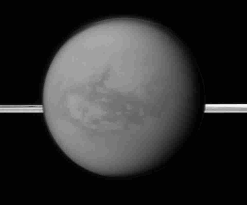 This image provided by NASA shows Titan with Saturn's rings in the background. A new study being released on Thursday suggests the dark areas near Titan's equator indicate the presence of a hydrocarbon lake and several ponds, a surprise to scientists who thought lakes only existed at the poles.