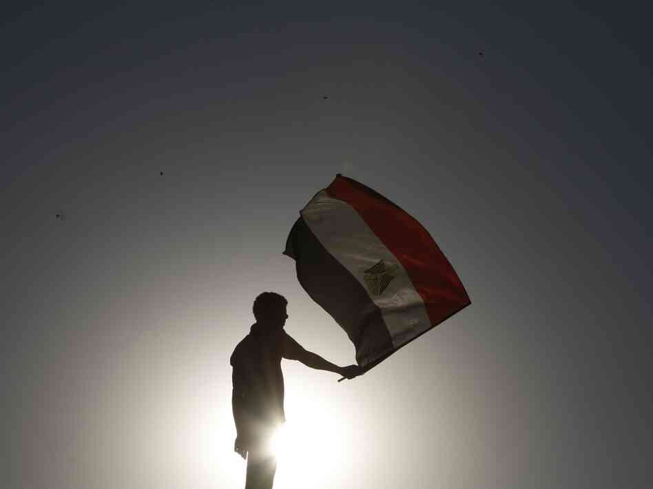 An Egyptian protester waves his national flag at sunset during a demonstration in Cairo's landmark Tahrir Square on June 5, 2012 to protest against verdicts handed down in ex-president Hosni Mubarak's murder trial.