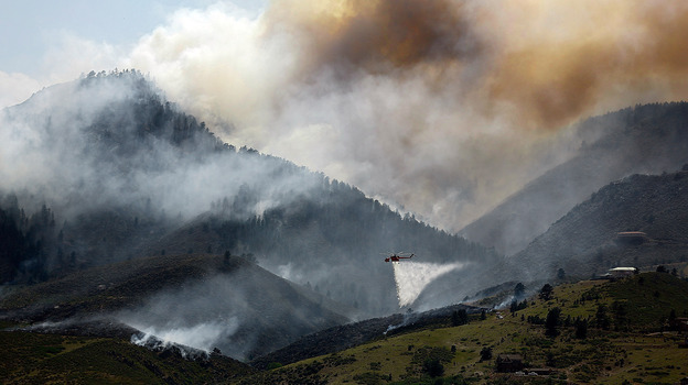 Near Laporte, Colo., earlier this week, smoke billowed from the mountains. In the foreground: A helicopter was dumping water on a hotspot. (Getty Images)